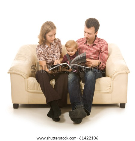 Family sitting on sofa together looking at book on white