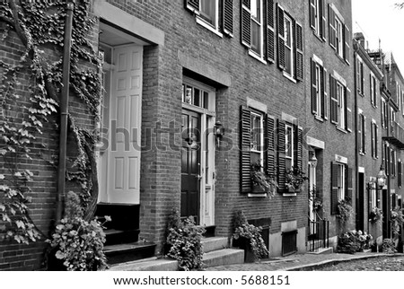 Famous Acorn Street, america's most photographed area in the Beacon Hill area of Boston Massachusetts, showing gas light, cobblestone road, shutters. - stock photo