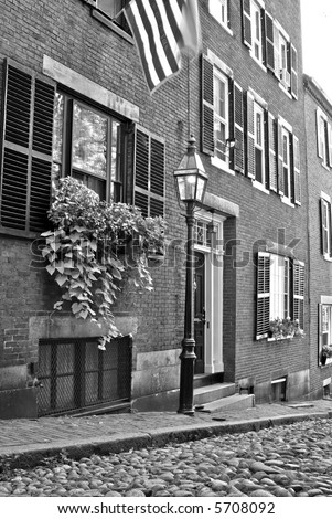 Famous Acorn Street, america's most photographed area in the Beacon Hill area of Boston Massachusetts, showing gas light, cobblestone road, shutters. american flag - stock photo