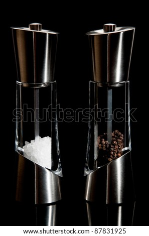 Fancy salt and pepper mills on a black background