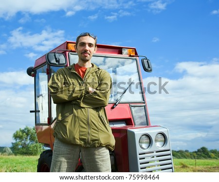 Farmer with tractor on meadow grass in summer day - stock photo
