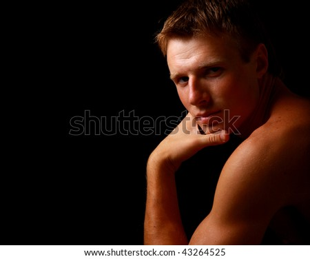 fashion male portrait on the floor over a black background - stock photo
