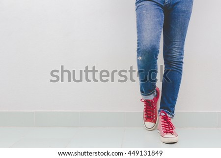 fashion man's legs in jeans and sneakers on floor
