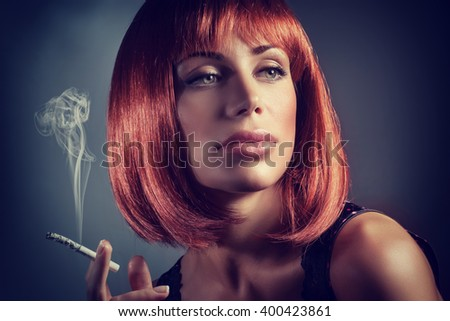 Fashion portrait of gorgeous redhead woman smoking in the studio over dark background, female with beautiful hairstyle and sensual look - stock photo