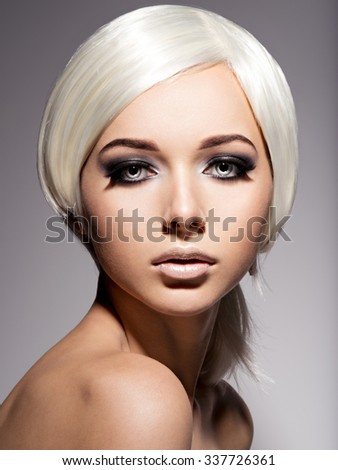 Fashion portrait of young woman with blond hairs and black makeup of eye - stock photo
