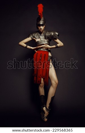 Fashion studio shot of beautiful woman in armor and in helmet with feathers on her head - stock photo