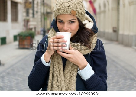 fashionable woman holding coffee outdoors - stock photo
