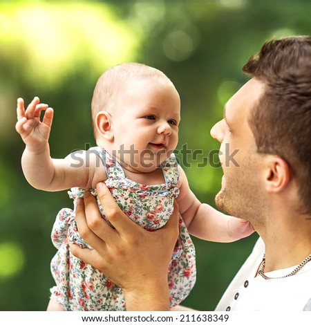 father and baby daughter playing in the park in lovedad and baby daughter playing in the park in love - stock photo