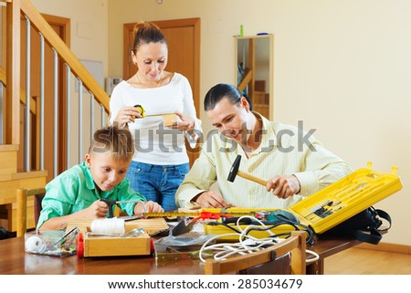Father and son are doing with their hands crafts in home, woman helps them - stock photo