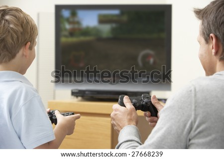 Father And Young Son Playing With Game Console - stock photo