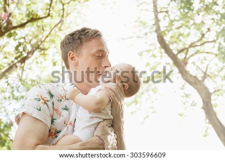 Father kissing his cute baby  outdoors in spring park against natural green background. low angle view. family shot - stock photo