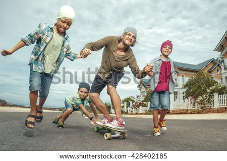 Father learning to ride skateboard as young boys him in the suburb street having fun - stock photo
