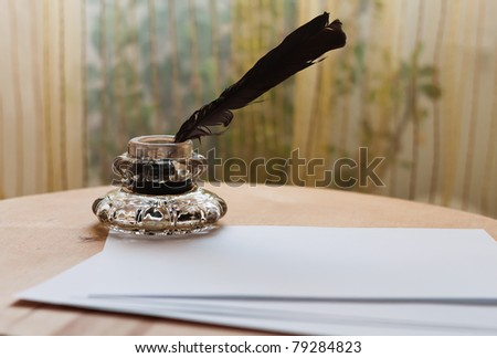 Feather and inkwell - stock photo