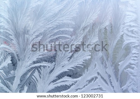 Feathery frost pattern - ice flowers on window glass. - stock photo