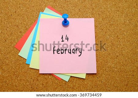 14 february written on color sticker notes over cork board background.