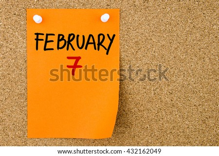 7 FEBRUARY written on orange paper note pinned on cork board with white thumbtacks, copy space available - stock photo