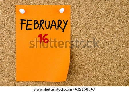 16 FEBRUARY written on orange paper note pinned on cork board with white thumbtacks, copy space available - stock photo