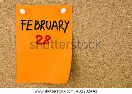 28 FEBRUARY written on orange paper note pinned on cork board with white thumbtacks, copy space available - stock photo