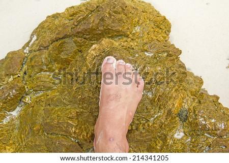 feet standing on a rock on a sandy beach - stock photo