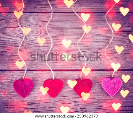 felt fabric love valentine's hearts hanging on rustic driftwood texture background with twine - stock photo