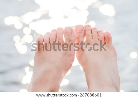 female feet against bokeh water - stock photo