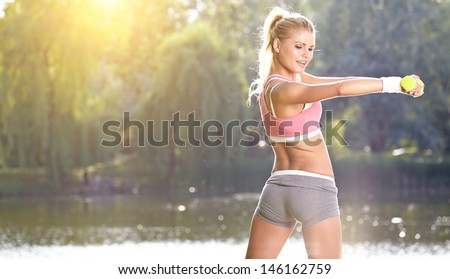 female fitness instructor exercising with small weights in green park  - stock photo