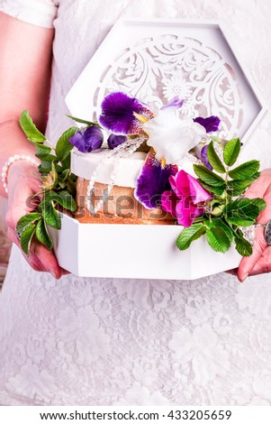 Female holding a Cake. Flower Topped Simple Wedding Cake. - stock photo