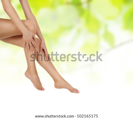 female legs over green natural background being massaged with hands - heathcare and hygiene concept - stock photo