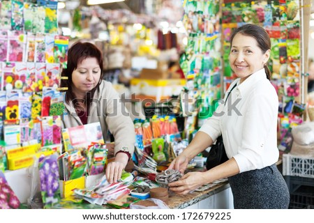 female mature gardener chooses solid fertilizer  at store for gardeners - stock photo