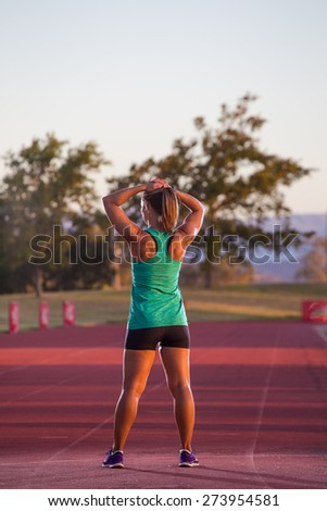 Female sprinter / athlete stands on a tartan race track stretching before a race.