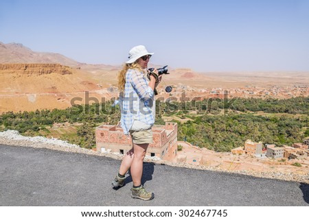 Female tourist taking pictures of Tinerhir - town near Todgha Gorge, Morocco - stock photo