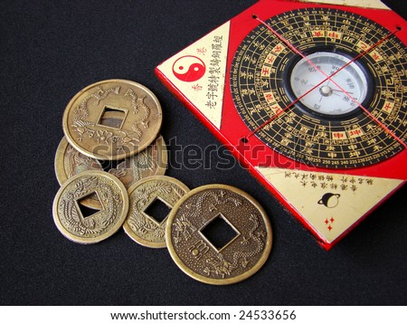Feng shui compass (Luopan) and chinese coins on black background - stock photo