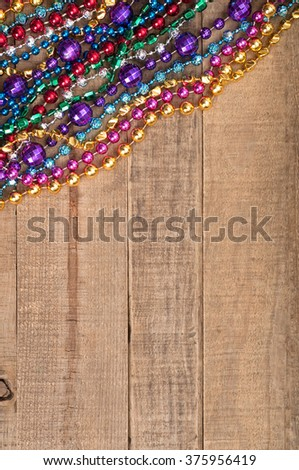 Festive Top View of Bright and Colorful Mardi Gras Bead Strands in upper corner on Rustic Brown, Textured Board Plank Background with Blank Space or Room for copy, text, your words.  Vertical