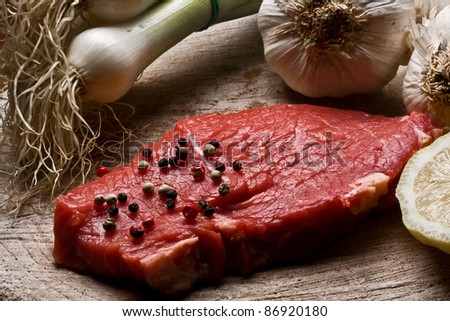 Fillet Mignon on wood with pepper and garlic - stock photo