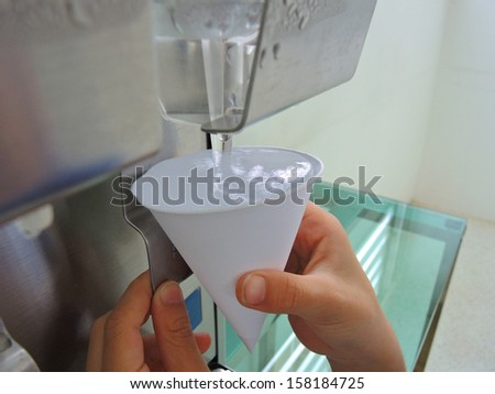 filling plastic cup at water cooler - stock photo