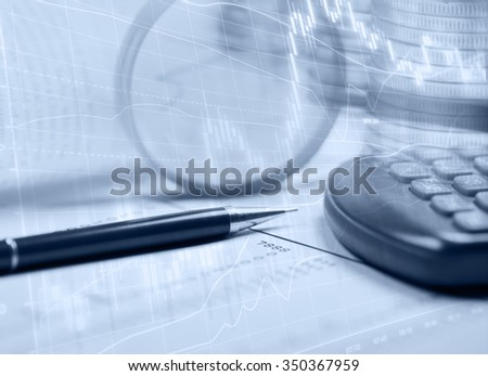 Financial graphs with a calculator, pen and magnifying glass reporting stock performance - stock photo