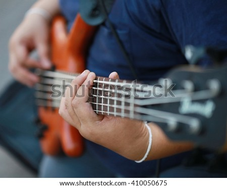 finger press guitar strings,  play guitar, close up finger play electric guitar with amplifier on concert stage, rock and roll concert, music tool and equipment. - stock photo