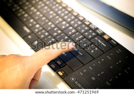 Finger pressing enter key.