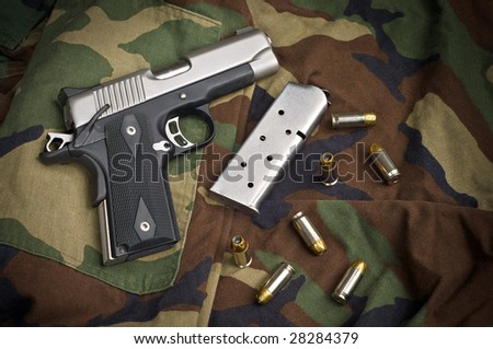 45 Firearm Pistol Clip And Hand Gun Ammunition on military camouflage background - stock photo