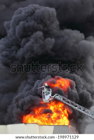 Firefighter and burning house. - stock photo