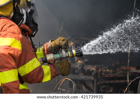2 firefighters spraying water in fire fighting operation - stock photo