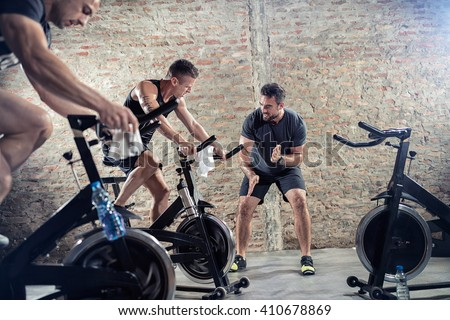 Fit young people on exercise bicycle  - stock photo