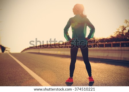fitness young woman runner in sportswear standing with her hands on hips on sunrise road - stock photo