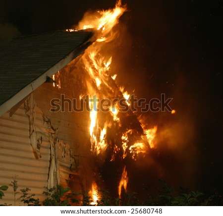 Flames shoot out from the roof and side of a house.