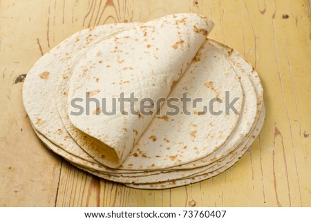 flour tortillas on wooden table - stock photo