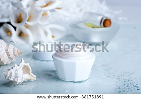 flower and jar of moisturizing face cream for spa treatment. - stock photo
