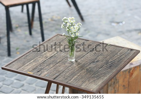 flower vase on wood table ,Still-Life with white hortensia flowers in glass vase outdoor, wood tables and black chairs set up for lunch outside cafe  - stock photo