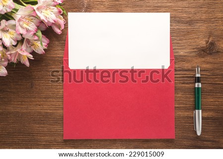 Flowers, envelope and pen on wooden background   - stock photo