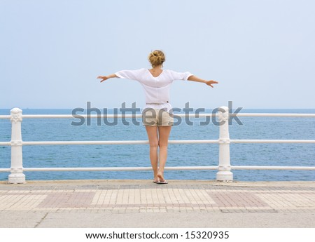 flying over the sea; woman facing the sea with her arms raised as if flying - stock photo