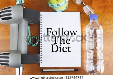 """""""Follow The Diet"""" text on notebook with delicious green apple, measure tape, spectacle, a bottle of mineral water, and bodybuilding tools on wooden background - healthy, exercise and diet concept - stock photo"""